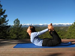 Bow Pose, yoga pose with the Sangre de Cristo Mountains, Colorado