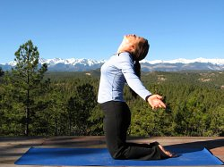 Modified Camel Pose, yoga pose with Sangre de Cristo mountains, Colorado