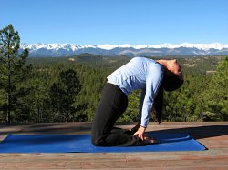 Camel Pose, yoga pose with Sangre de Cristo Mountains, Colorado