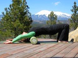 Shoulder stretch on foam roller, bridge position, arms over head.