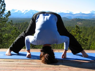 Wide-legged standing forward bend yoga pose with a view o the Sangre de Cristo Mountains, Colorado