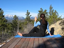 Modified Half Spinal Twist yoga pose, with view of Spanish Peaks, Colorad