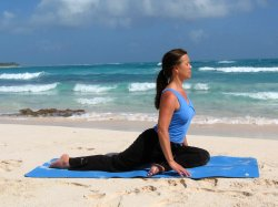 Yoga Pigeon Pose, on beach near Playa del Carmen, Mexico