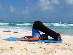 Plow Pose, yoga pose at beach near Playa del Carmen, Mexic