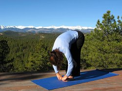 Standing Forward Bend yoga pose with the Sangre de Cristo Mountains, Colorado