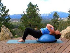 Classic crunch beginnning position on the Bosu Balance trainer.