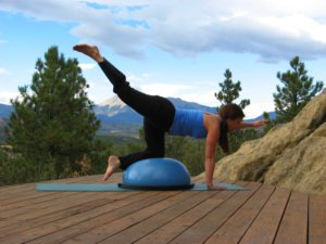 Bosu balance trainer, kneeling, one arm raised and opposite leg raised.