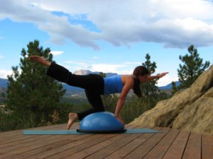 Bosu ball, kneeling with one arm raised and opposite leg raised.