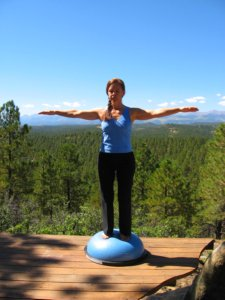 Standing Balance on Bosu Ball with arms out in Cross position.
