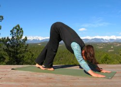 Downward Dog yoga pose with Leg Crossover, view of Sangre de Cristo Mountains, Colorad