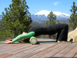 Shoulder stretch on foam roller, bridge position, arms over head.