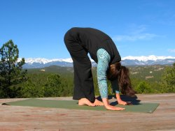 Standing Forward Bend yoga pose with Leg Crossover and view of Sangre de Cristo mountains, Colorad