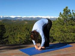 Standing Forward Bend yoga pose with the Sangre de Cristo Mountains, Colorado