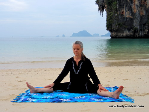 Photo of Elle Bieling doing Dragonfly Pose in Yin Yoga, on Pranang Beach, Railay, Thailand