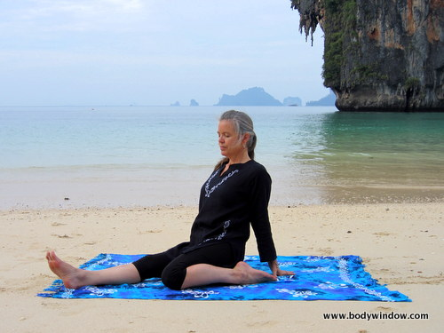 Photo of Elle Bieling doing Saddle Pose in Yin Yoga on Pranang Beach, Railay, Thailand