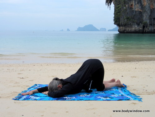 Photo of Elle Bieling doing Quarter Dog Pose in Yin Yoga on Pranang Beach, Railay, Thailand