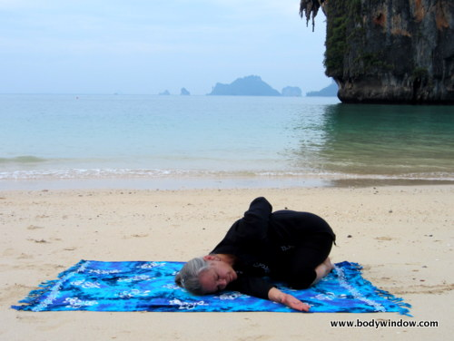 Photo of Elle Bieling doing Wide-Knee Child's Pose with a Twist in Yin Yoga, on Pranang Beach, Railay, Thailand